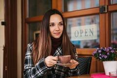 La muchacha hermosa joven bebe el café o el chocolate caliente en un café de la calle Foto de archivo libre de regalías