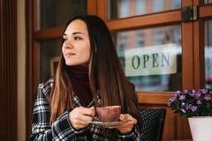 La muchacha hermosa joven bebe el café o el chocolate caliente en un café de la calle Foto de archivo