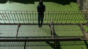 La muchacha hermosa joven camina en el puente oxidado arruinado fino del metal sobre el agua verde almacen de metraje de vídeo