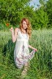 La muchacha hermosa joven camina entre los oídos del trigo en el campo en los sundress blancos elegantes en el fondo Imagenes de archivo
