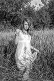 La muchacha hermosa joven camina entre los oídos del trigo en el campo en los sundress blancos elegantes en el fondo Fotos de archivo libres de regalías