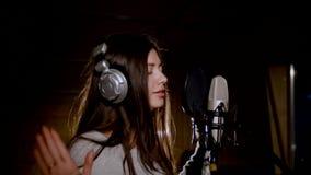 La muchacha hermosa joven canta Cantante joven que canta en un micrófono Retrato cercano para arriba del cantante Estudio de grab fotos de archivo