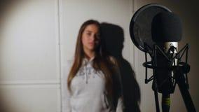 La muchacha hermosa joven canta Cantante joven que canta en un micrófono Retrato cercano para arriba del cantante Estudio de grab fotografía de archivo
