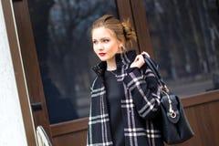 La muchacha hermosa joven con el bolso de moda se está colocando en el s Imagenes de archivo