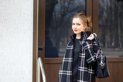 La muchacha hermosa joven con el bolso de moda se está colocando en el s Fotografía de archivo libre de regalías