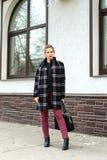La muchacha hermosa joven con el bolso de moda se está colocando en el s Fotos de archivo libres de regalías