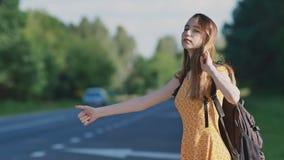La muchacha hermosa joven con el pelo largo en un vestido y una mochila en ella detrás está cogiendo un coche en la autopista sin almacen de video