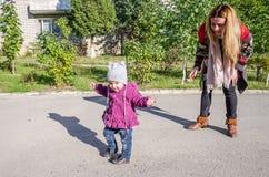 La muchacha hermosa joven con el pelo largo en una madre de la chaqueta enseña a su hija a caminar los primeros pasos de su bebé  Foto de archivo