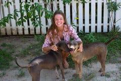 La muchacha hermosa joven con el pelo largo juega con los perros Imágenes de archivo libres de regalías