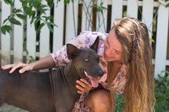 La muchacha hermosa joven con el pelo largo juega con los perros Fotos de archivo libres de regalías