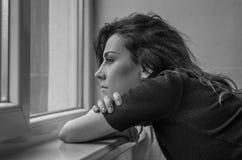 La muchacha hermosa joven con el pelo largo mira hacia fuera la ventana Fotografía de archivo