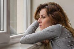 La muchacha hermosa joven con el pelo largo mira hacia fuera la ventana Fotos de archivo