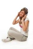 La muchacha hermosa joven con los auriculares Imágenes de archivo libres de regalías