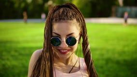 La muchacha hermosa joven con teme el bailar en un parque Mujer hermosa en vaqueros y gafas de sol que escuchan la música y almacen de metraje de vídeo