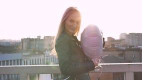 La muchacha hermosa joven con un globo en la forma de un corazón se coloca cerca de la verja en el tejado en la puesta del sol almacen de metraje de vídeo