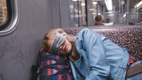 La muchacha hermosa joven de la cámara lenta en la venda en los ojos, se cayó dormido en el metro La cabeza puso una mochila almacen de metraje de vídeo