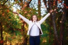 La muchacha hermosa joven del adolescente lanza las hojas de otoño coloridas en parque Imagenes de archivo
