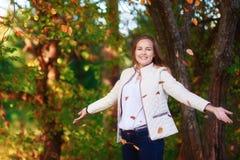 La muchacha hermosa joven del adolescente lanza las hojas de otoño coloridas en parque Imágenes de archivo libres de regalías