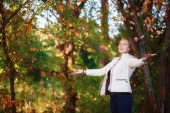 La muchacha hermosa joven del adolescente lanza las hojas de otoño coloridas en parque Fotografía de archivo
