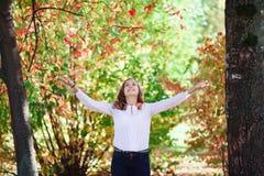 La muchacha hermosa joven del adolescente lanza las hojas de otoño coloridas en parque Fotos de archivo