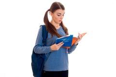 La muchacha hermosa joven del estudiante con la mochila lee un libro y una presentación aislada en el fondo blanco en estudio Fotos de archivo libres de regalías