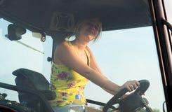 La muchacha hermosa, joven del granjero está conduciendo el tractor Foto de archivo