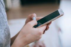 La muchacha hermosa joven del inconformista con el teléfono móvil en manos escribe el mensaje de texto imagenes de archivo