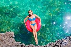 La muchacha hermosa joven en bikini nada en un mar tropical en un rubb imagen de archivo libre de regalías