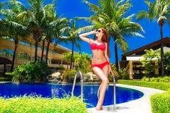 La muchacha hermosa joven en bikini rojo está al lado de la piscina en ho fotografía de archivo libre de regalías