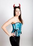La muchacha hermosa joven en corsé azul con los cuernos rojos parece diablo bonito Fotografía de archivo libre de regalías