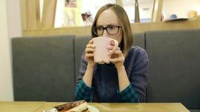 La muchacha hermosa joven en muchacha de los vidrios hizo muecas después de intentar té insípido en un café Chocan al cliente des almacen de video