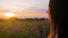 La muchacha hermosa joven en el campo mira el sol poniente Ciérrese encima de tiro almacen de video