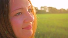 La muchacha hermosa joven en el campo mira el sol poniente Ciérrese encima de tiro Cámara lenta almacen de video