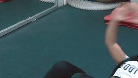 La muchacha hermosa joven en el gimnasio bombea los músculos de la prensa, mintiendo en el karemate, cierre para arriba almacen de metraje de vídeo