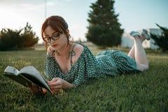 La muchacha hermosa joven en el vestido del cortocircuito del verano lee un libro que se sienta en la hierba imagen de archivo libre de regalías