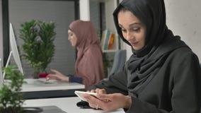 La muchacha hermosa joven en hijab negro se sienta en oficina y utiliza smartphone Muchacha en hijab negro en el fondo árabe metrajes