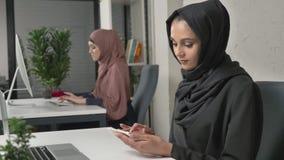 La muchacha hermosa joven en hijab negro se sienta en oficina y utiliza smartphone Muchacha en hijab negro en el fondo árabe almacen de video