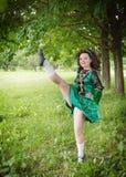 La muchacha hermosa joven en irlandés baila el baile del vestido al aire libre Imagen de archivo
