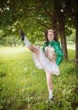 La muchacha hermosa joven en irlandés baila el baile del vestido al aire libre Fotos de archivo