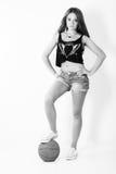 La muchacha hermosa joven en pantalones cortos con la bola se coloca en el estudio en el fondo blanco Foto de archivo