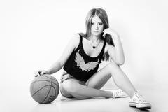 La muchacha hermosa joven en pantalones cortos con la bola se sienta en el estudio en el fondo blanco Imagen de archivo