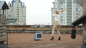 La muchacha hermosa joven en tacones altos rompe el monitor con un palo Palo, violencia, odio, anarquía, destrucción, tejado 60 almacen de video