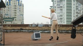 La muchacha hermosa joven en tacones altos rompe el monitor con un palo Palo, violencia, odio, anarquía, destrucción, tejado 60 metrajes
