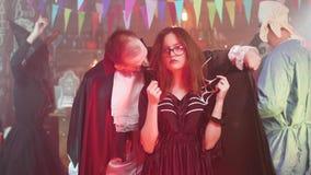 La muchacha hermosa joven en traje de la bruja consigue mordida por un vampiro en un partido de Halloween almacen de metraje de vídeo