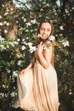 La muchacha hermosa joven en un vestido largo y la guirnalda de flores acercan al arbusto de lila del jardín Foto de archivo