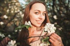 La muchacha hermosa joven en un vestido largo y la guirnalda de flores acercan al arbusto de lila del jardín Foto de archivo libre de regalías