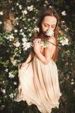 La muchacha hermosa joven en un vestido largo y la guirnalda de flores acercan al arbusto de lila del jardín Imagen de archivo libre de regalías