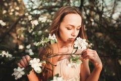 La muchacha hermosa joven en un vestido largo y la guirnalda de flores acercan al arbusto de lila del jardín Fotografía de archivo libre de regalías
