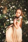 La muchacha hermosa joven en un vestido largo y la guirnalda de flores acercan al arbusto de lila del jardín Imágenes de archivo libres de regalías