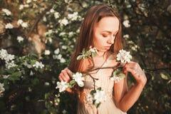 La muchacha hermosa joven en un vestido largo y la guirnalda de flores acercan al arbusto de lila del jardín Fotos de archivo libres de regalías